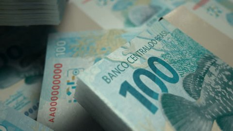 An extreme closeup pan across variously placed bundled wads of brazilian real banknotes