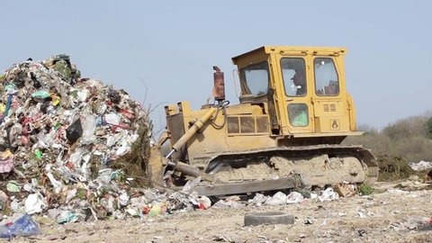 5/35 SRBIJA,KRUSEVAC,2014. Bulldozer (tractor) pushes a pile of trash at landfill. Vehicle flattening garbage to waste. Bulldozer moves non biodegradable garbage at the dump. Dogs searching food.25fps