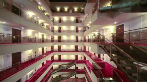 View from downward movement elevator to floors with balconies and many doors in hotel