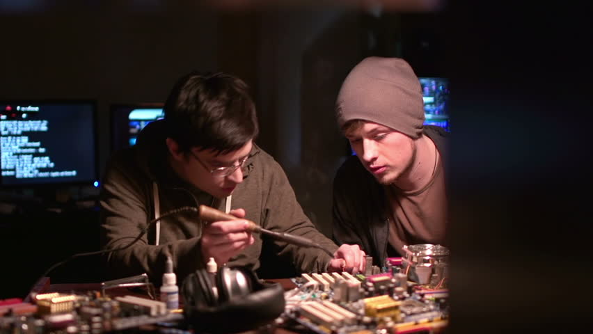 Dolly from left to right of two men soldering system board of computer