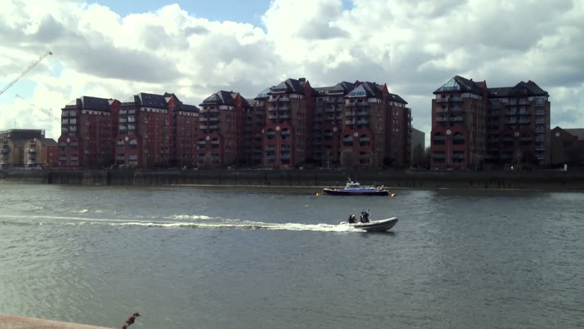 Rigid hull inflatable dinghy (Rib) goes past near Chelsea on the River Thames London.
