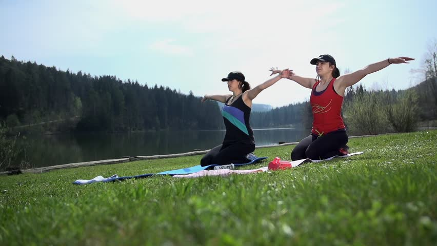 Two Pretty Ladies Doing Breathing Yoga Exercise At Lake
