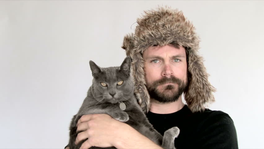 Model released man in studio holding Russian Blue cat while wearing funny Russian hat.