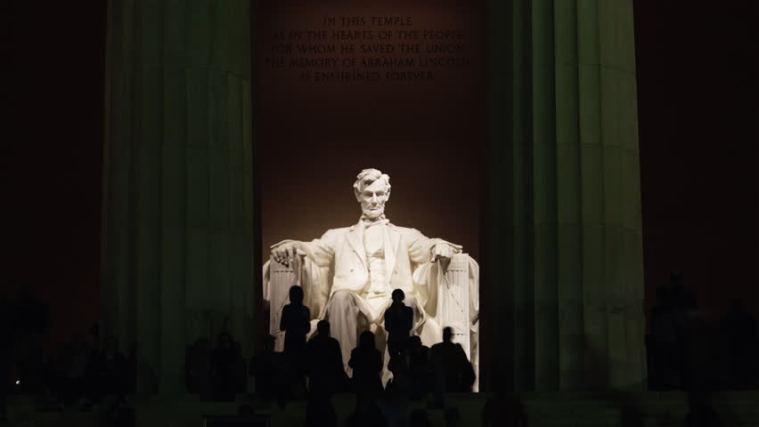 Time lapse Wide Shot Silhouettes of people in front of Abraham Lincoln statue at Lincoln Memorial illuminated at night, Washington D.C, USA