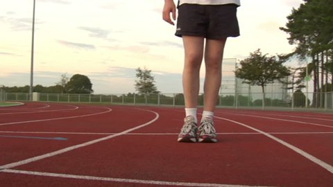 A runners feet from a unique vantage point on a running track.