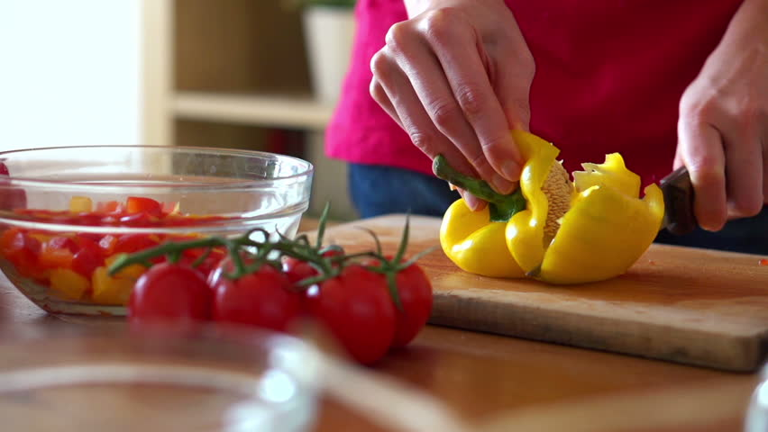 Slicing yellow pepper on chopping board, super slow motion, shot at 240fps