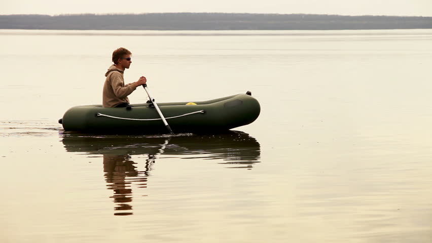 Tranquil man rowing in Inflatable boat on the quiet lake