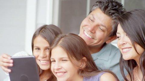 A family sits on a bench and takes a selfie with a tablet