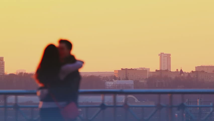 Young couple kissing at sunset with a city view in the background. Romantic moments