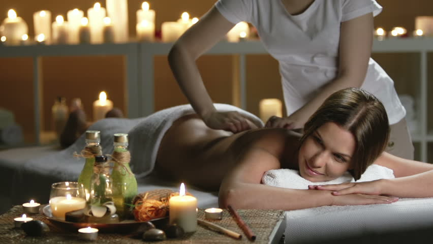 Groomed woman lying on daybed massaged by unrecognizable woman