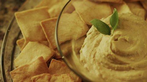 Panning close up high angle shot of pita chips and hummus