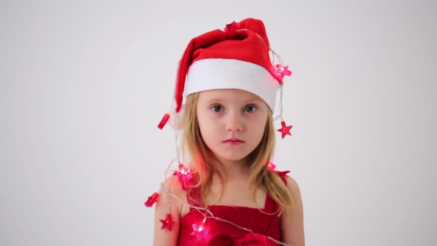 c6d25756b Cute little girl in a red dress wrapped the garland with bell Santa Claus