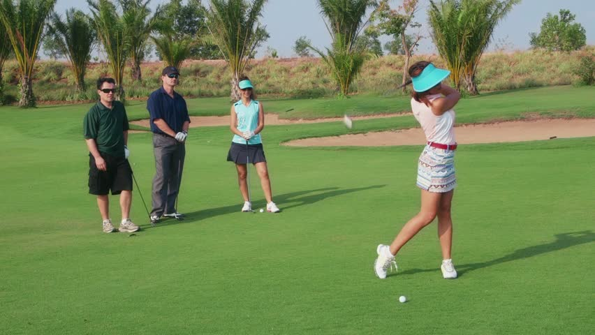 People, sport, leisure activities, recreation and lifestyle, golf in country club during summer holidays. Asian woman playing golf near hole, group of friends watching. 10of30