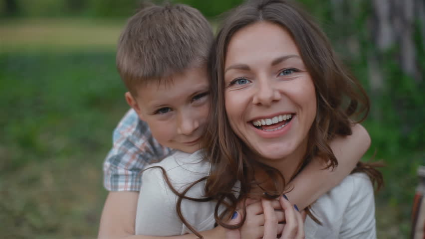 Young attractive mother and son looking into the camera . They are very happy and cheerful