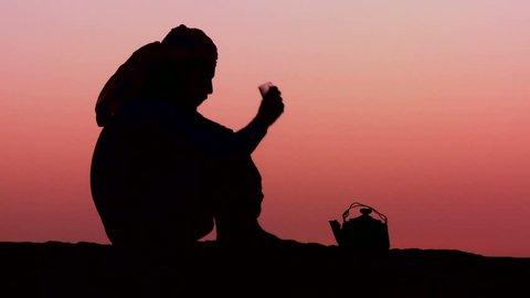 WADI RUM, JORDAN CIRCA 2013 - A Bedouin man pours tea in silhouette against the sunset.