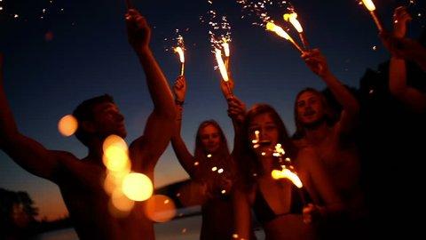 Friends with sparklers dancing in slow motion
