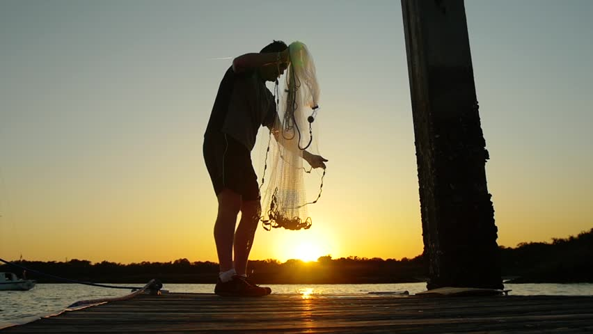 Man casting a shrimping net at sunrise sunset super slow motion stock footage video clip