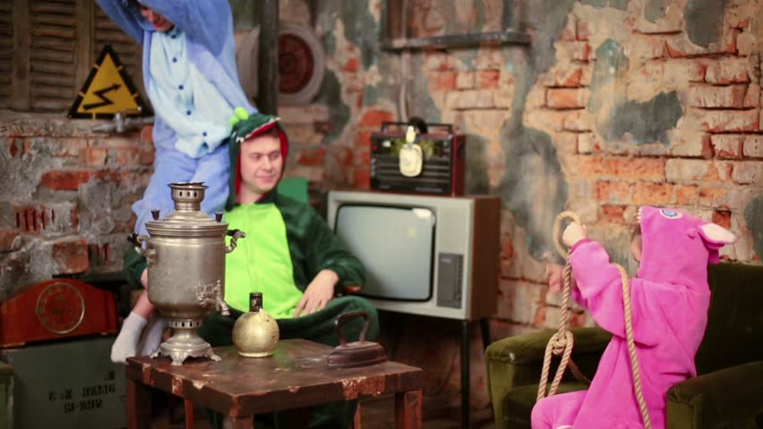 Family in colorful costumes of dragons pose at very old room with table and samovar.