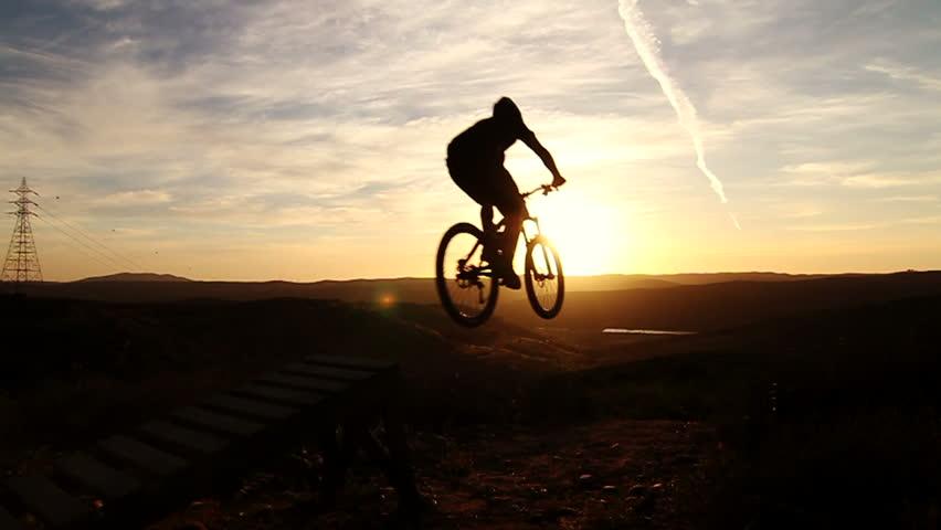 Slow Motion Silhouette Mountain Biking Off Extreme Jump  #6261950