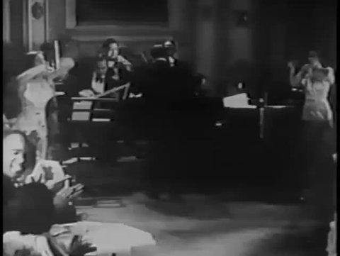Wide shot of tap dancers performing in nightclub, 1930s