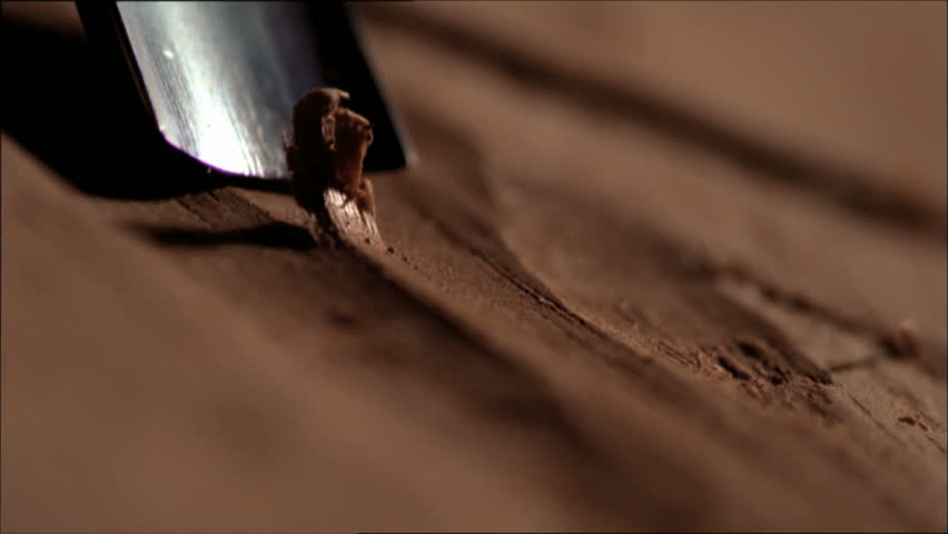 Extreme close up of carpenter chiseling, shaping and sanding wood work
