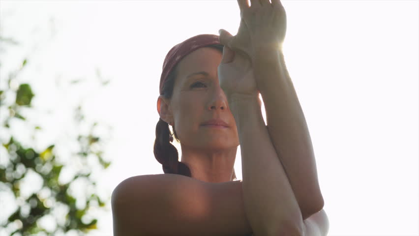 Close Up Woman doing yoga standing against sun / Ravello, Campania, Italy