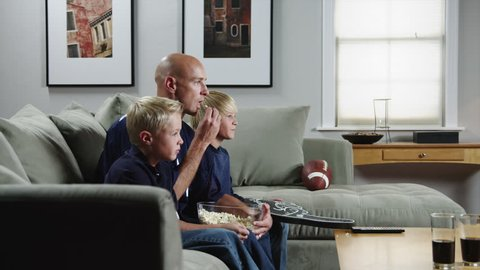 Medium Shot Father with two sons (8-9, 10-11) watching match in TV and eating popcorn