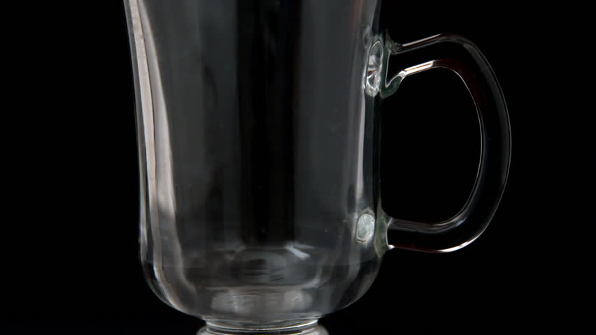 Hot water pouring over tea bag in glass in slow motion