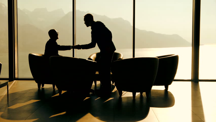 Business meeting. 2 businessman having a conversation. discussion talking. silhouette. business background. handshake. company career corporate. cooperation. professionals. modern luxury interior | Shutterstock HD Video #6344360