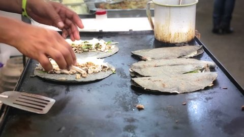 Mexican food, cooker prepares black maize tortillas with cheese and squash blossom
