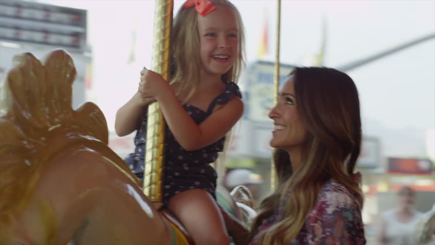 Close up of mother and daughter riding carousel at carnival