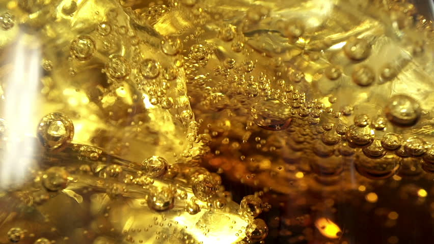 Pouring Cola with ice and bubbles in the glass. Close up soda soft drink. Food background. Slow motion filmed at 250 fps.