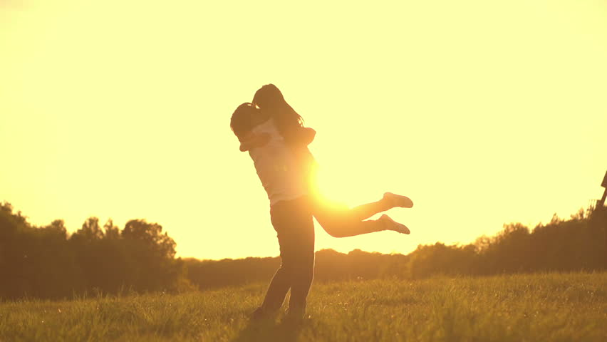 Romantic young couple silhouette. Woman is running to her man, they hug and spin around on a sunset with sun shining bright behind them on a horizon. Slow motion filmed at 250 fps.