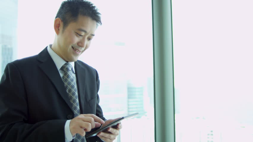 Young male Asian Chinese financial consultant using wireless tablet modern boardroom city skyscraper portrait shot on RED EPIC | Shutterstock HD Video #6374240