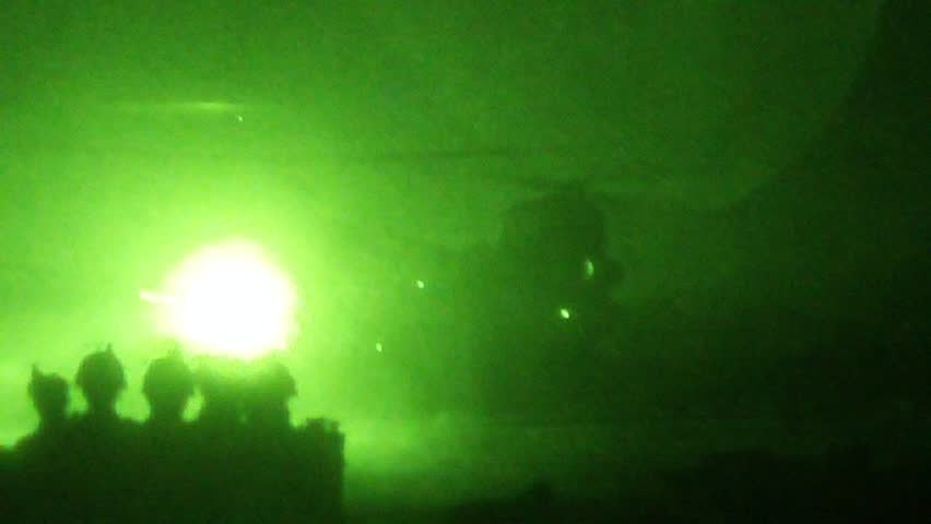 Night Vision: Chinook helicopter lands in desert at night silhouetted by soldiers in the foreground