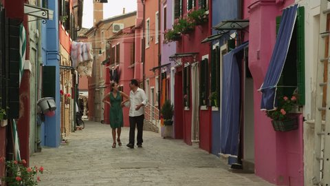 Wide Shot Couple walking on narrow street of old town / Murano, Venice, Italy