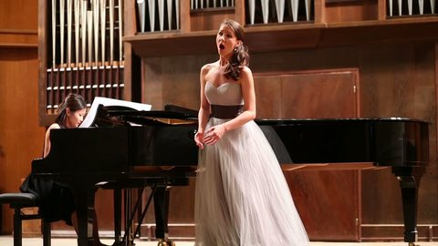 Woman pianist plays the piano and beautiful singer emotionally sing opera song
