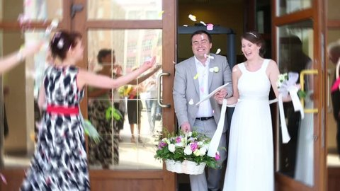 Newlyweds out of the registrars office and showered with rose petals