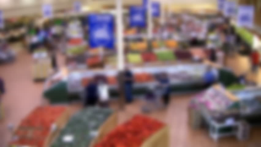 "Defocused, ""time lapse"" shot of modern supermarket. Shoppers in the fruit and vegetable section. Great background to overlay a graphic, logo, or text bar."