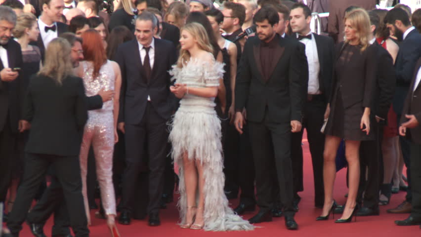 CANNES, FRANCE - MAY 2014: Kristin Stewart wearing a silver Chanel Couture ensemble with Chloe Grace Moretz, wearing a Chanel Couture gown with a high-low hemline and feather accents
