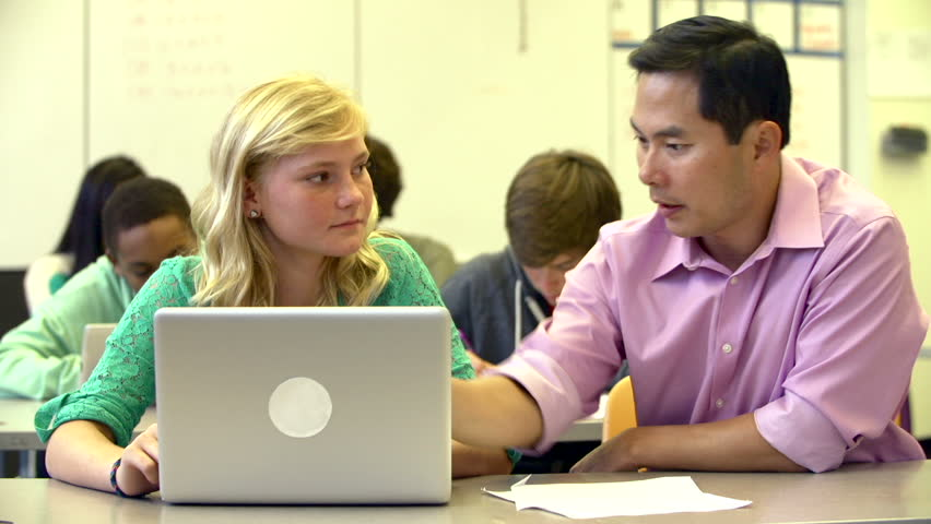 Female High School Student With Teacher Using Laptop
