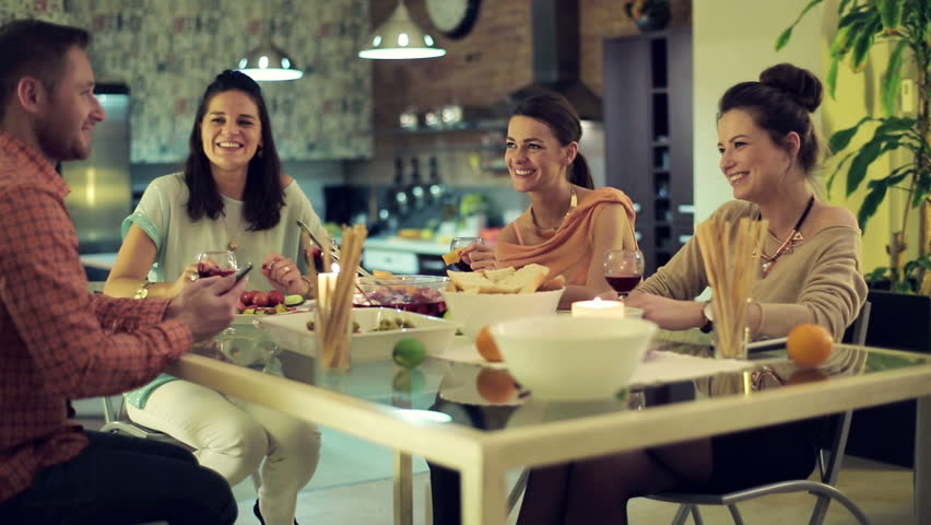 Friends looking at funny things on smartphone during dinner