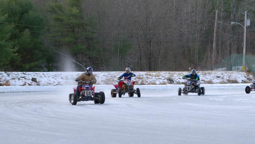 Sturbridge, Massachusetts - February 7, 2014: ATV riders compete in ice racing on frozen pond - 240 fps slow motion