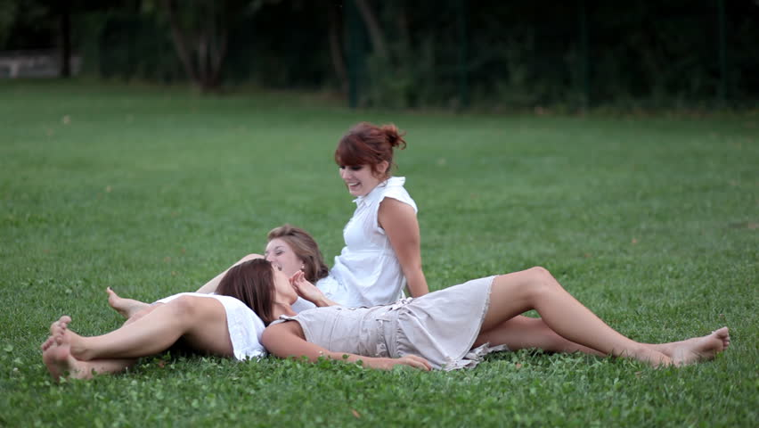 Three beautiful young girls lying on the grass outdoors in a park, chatting, laughing, having great time