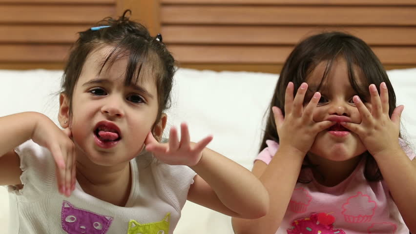 Small girls making a funny face in the bedroom