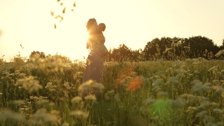 Young pregnant woman holding a baby daughter. Beautiful sunset in the meadow. Dolly shot. #6524240