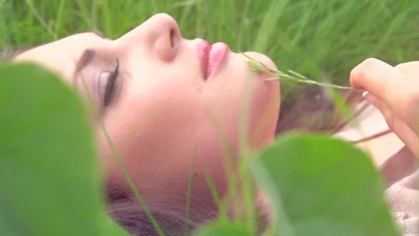 Beautiful Girl Lying on the Meadow and Dreaming. Green grass. Enjoy Nature. Beauty Woman outdoors. Spring Field. Close up Slow Motion Footage 1920x1080p. Slowmo. 1080p full HD. High speed camera shot #6532190