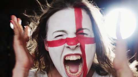 Female soccer fan with England flag on the face screaming into a camera