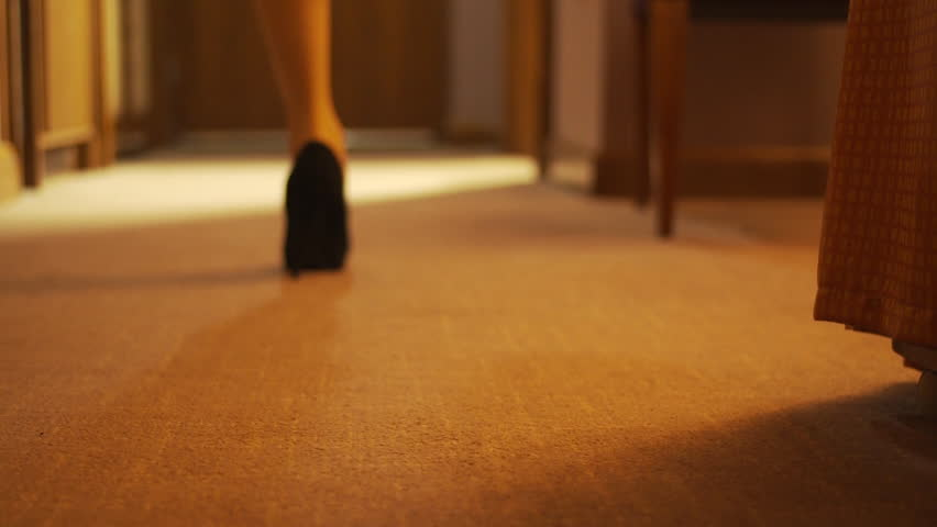 Beautiful young girl walking into frame in high heels in her hotel room before taking them off and walking to the bathroom. Shot focuses on the stiletto shoes.