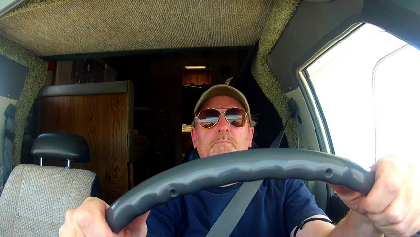 A shot of a mature or middle aged man in the cab of an RV driving down the highway.